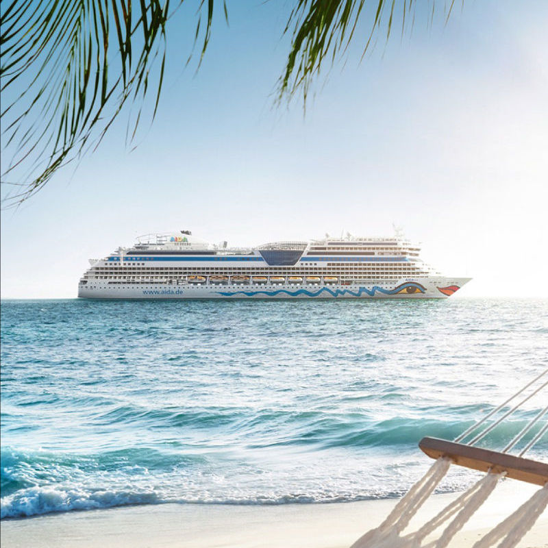 Strand, im Hintergrund ein AIDA Schiff im Meer