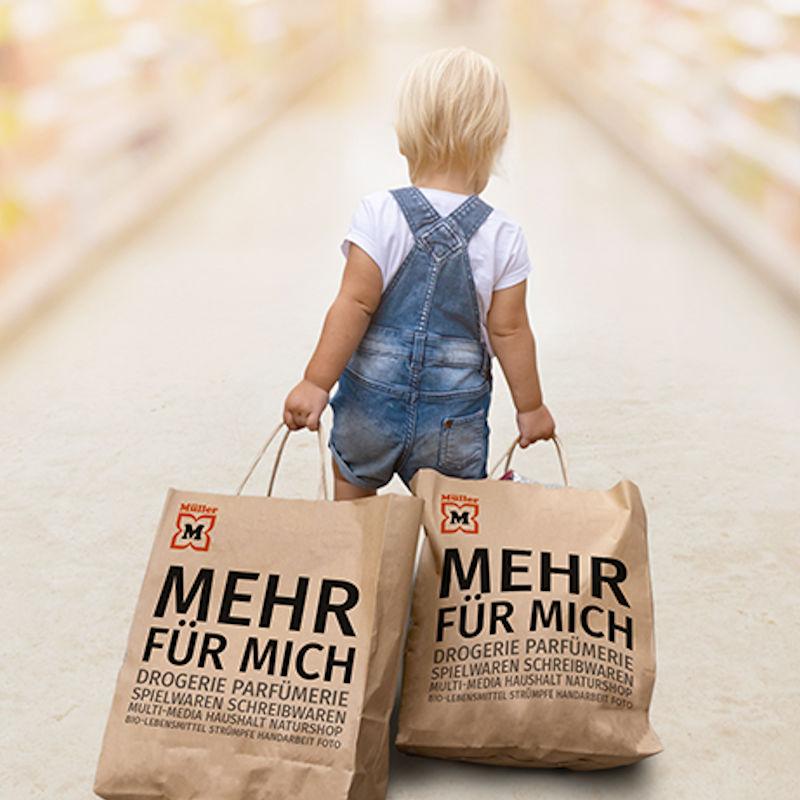 kleiner Junge mit zwei Müller-Einkaufstasche, welche er hinter sich her schleift.